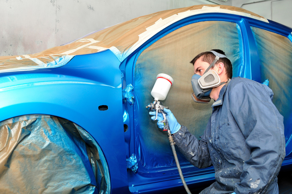 Painter working with blue car.